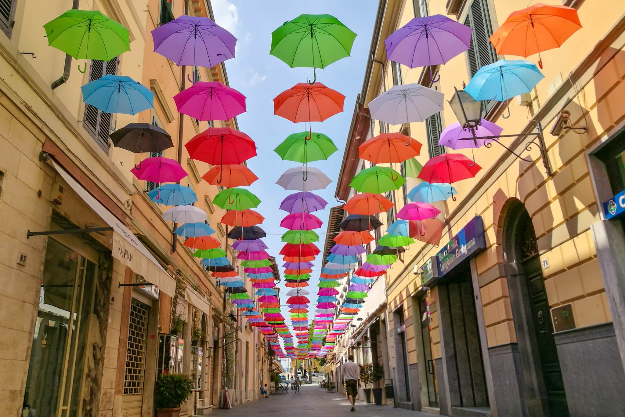 a person walking in Via Mazzini under the floating umbrellas in Pietrasanta
