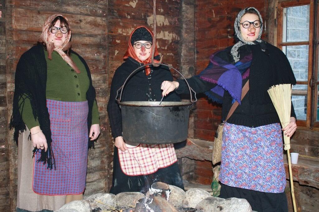La Befana - three ladies dressed like Befana  around the fire.