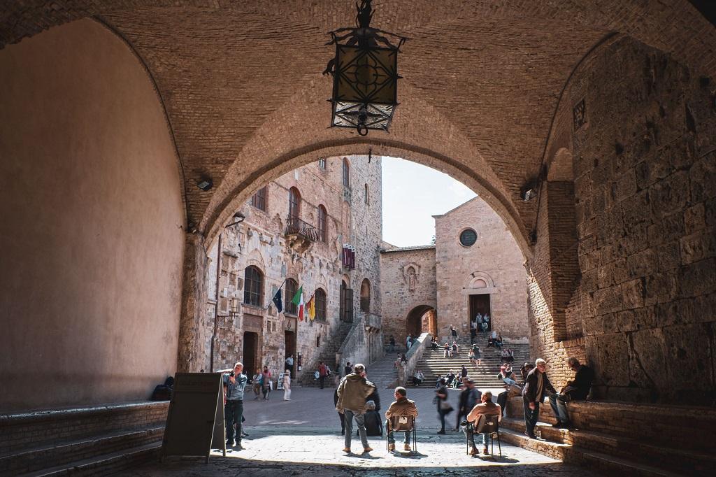 nonni resting in the sun in the piazza del Duomo in San Gimignano
