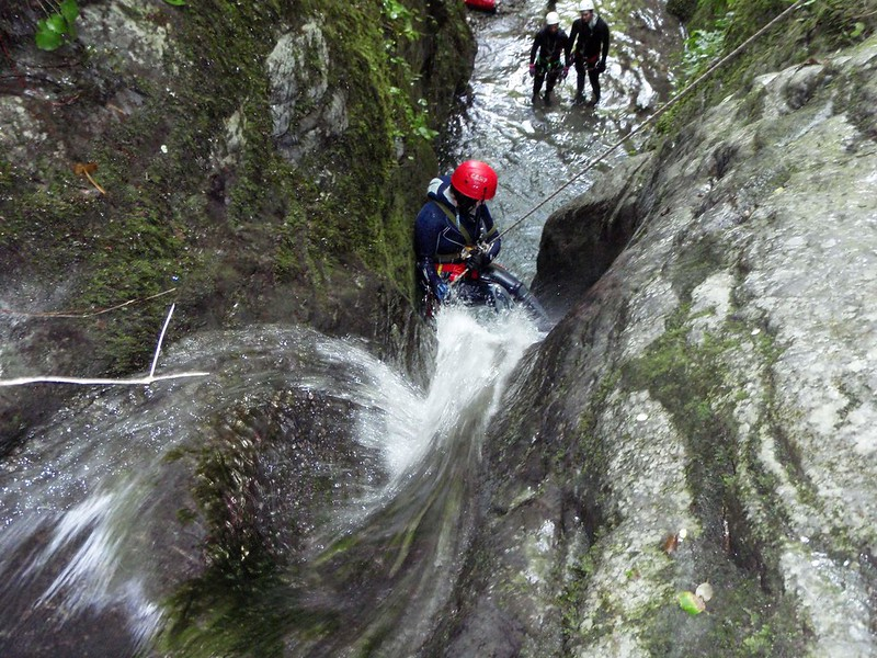A person descending a rock with a rope while doing canyoning along the Rio Selvano Stream in Tuscany